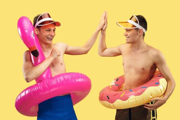 Geïsoleerd portret van twee jonge mensen van halve lengte. glimlachende vrienden in petten met zwembanden. gezichtsuitdrukking, zomer-, weekend-, resort- of vakantieconcept. trendy kleuren.