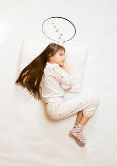 Geïsoleerd schot van bovenaanzicht van schattig meisje slapen op groot kussen met tekstballon