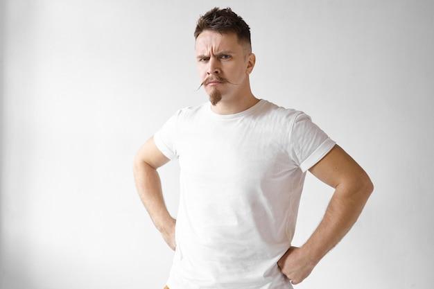 Geïsoleerd schot van boze sombere stijlvolle jonge europese man wint stoppels en snor, fronsende wenkbrauwen en handen op zijn middel, woede uiten, boos zijn op zijn zich misdragende kinderen