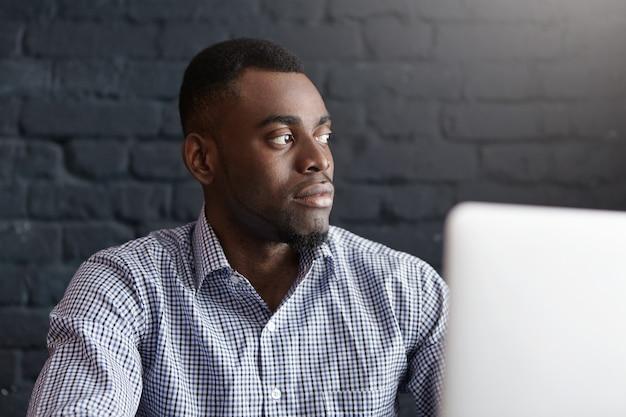 Geïsoleerd schot van ernstige jonge donkere mannelijke freelancer die blauw geruit overhemd draagt