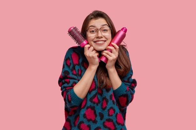 Geïsoleerd schot van gelukkige jonge vrouw met donker haar, houdt noodzakelijke dingen voor het maken van kapsel dichtbij gezicht
