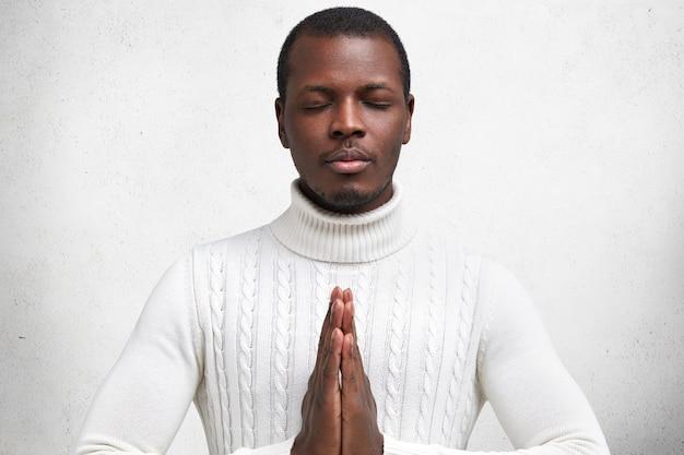 Geïsoleerd schot van knappe donkere man houdt de handen voor zich, de handpalmen tegen elkaar gedrukt, hoopt op het beste en bidt, ogen dicht