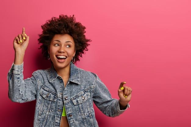 Geïsoleerd schot van positieve gelukkige vrouw danst en kijkt bedachtzaam opzij, heft de armen op, is op een discoparty, dresed in denim kleding, geïsoleerd op roze muur, vrije ruimte voor uw promotionele inhoud