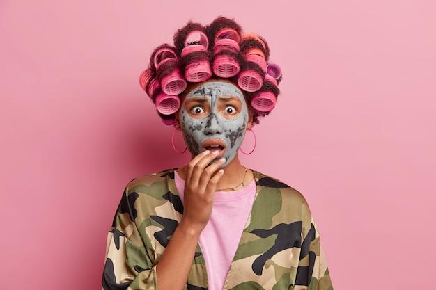 Geïsoleerd schot van verraste afro-amerikaanse vrouw die er beschaamd uitziet en schoonheidsprocedures ondergaat, draagt haarrollers die een kleimasker voeden dat over roze muur wordt geïsoleerd. gezichtsverzorging concept