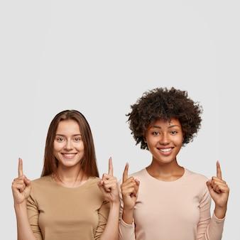 Geïsoleerd schot van vrolijke vrouwen van verschillend raspunt met beide omhoog wijsvingers