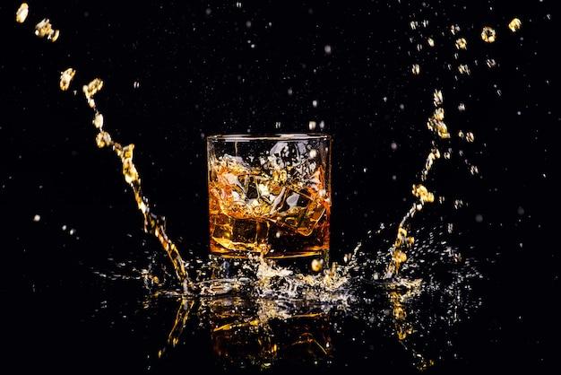 Geïsoleerd schot van whisky met plons