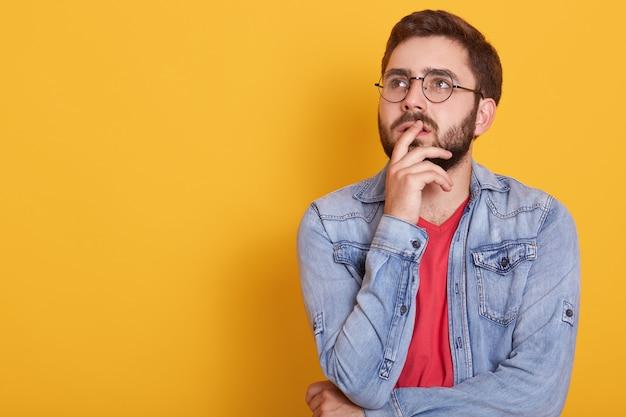 Geïsoleerd studioschot van de jonge knappe gebaarde mens die trendy denimjasje en overhemd dragen, die opzij ernstig en peinzend kijken. kaukasisch mannetje dat zich over geel bevindt