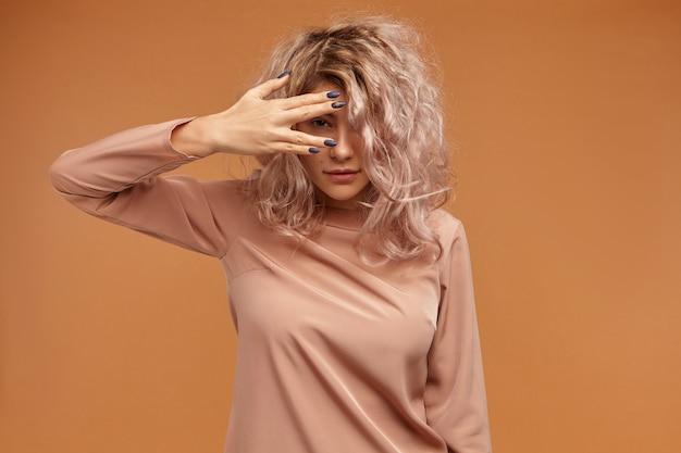 Geïsoleerd van schattige mysterieuze jonge europese vrouw met roze volumineus haar die hand voor haar oog houdt, naar je gluurt door de vingers, met een nieuwsgierige speelse blik