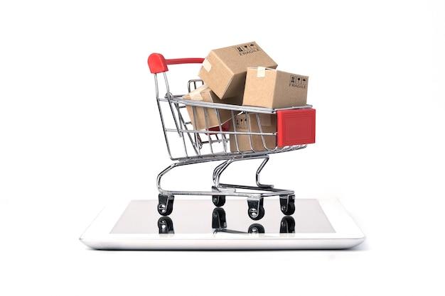 Geïsoleerd van verzending papieren dozen binnen rode winkelwagen trolley op tablet met witte achtergrond en kopie ruimte, online winkelen en e-commerce concept.