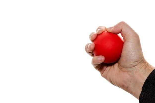 Geïsoleerde afbeelding van een persoon die een rode bal knijpt