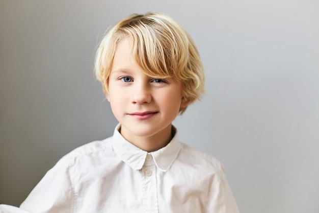 Geïsoleerde afbeelding van emotionele vrolijke blauwe ogen blanke jongen met blond haar met speelse gezichtsuitdrukking. kinderen, spontaniteit, gelukkige jeugd en positieve emoties