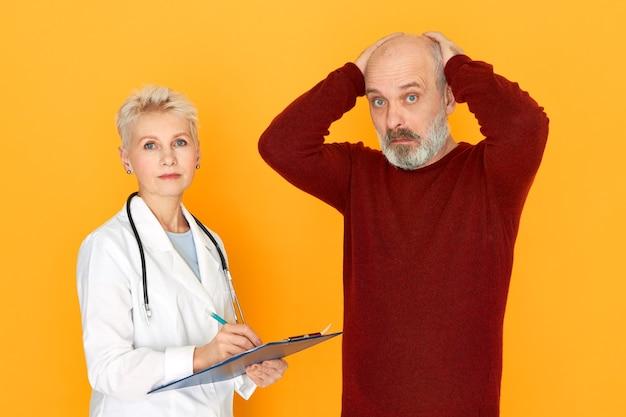 Geïsoleerde afbeelding van geschokt ongeschoren senior man hand in hand op zijn kale hoofd wordt gediagnosticeerd met diabetes tijdens medisch overleg met volwassen vrouwelijke arts. gezondheid, ziekte en behandeling