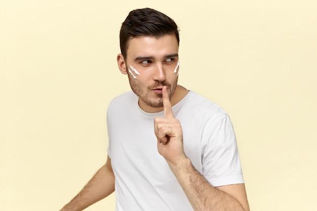 Geïsoleerde afbeelding van mysterieuze jonge man gekleed in een casual wit t-shirt met wijsvinger op de lippen, vragen om stil te zijn en zijn geheim niet aan andere mensen te vertellen.