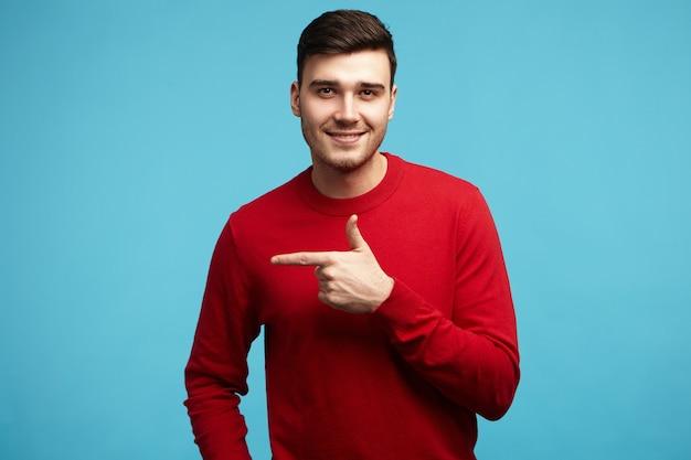 Geïsoleerde afbeelding van positieve modieuze jonge man met stijlvolle kapsel en haren glimlachen naar de camera