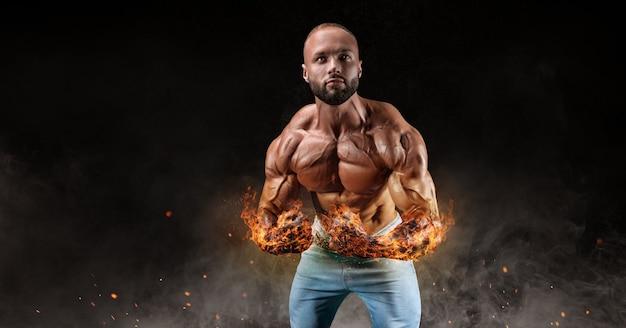 Geïsoleerde atleet op een achtergrond van rook met brandende handen. vetverbranding concept. bodybuilding. gemengde media