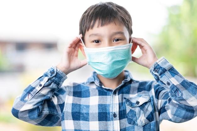 Geïsoleerde aziatische jongen jongenskinderen zetten een groen masker op de juiste manier gezicht neus mond, concept van bescherming tegen corona virusziekte, ziektekiemen en in de lucht geboren transmissie