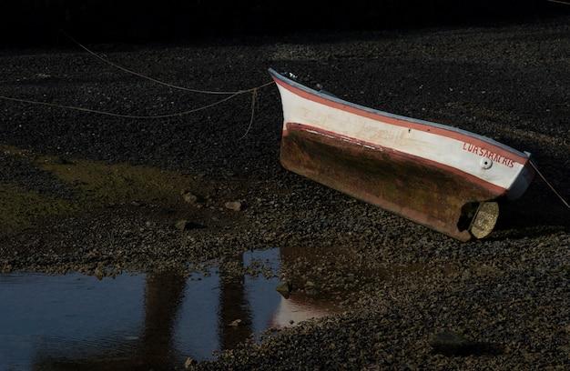 Geïsoleerde boot aan de grond naast de zee