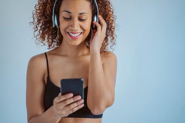 Geïsoleerde casual vrouw luisteren naar funky muziek met behulp van draadloze hoofdtelefoons. afro-cultuur levensstijlen. jonge afro-amerikaanse vrouw met smartphone.