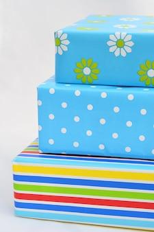 Geïsoleerde close-up verticale shot van geschenkdozen in kleurrijke verpakking gestapeld bovenop elkaar