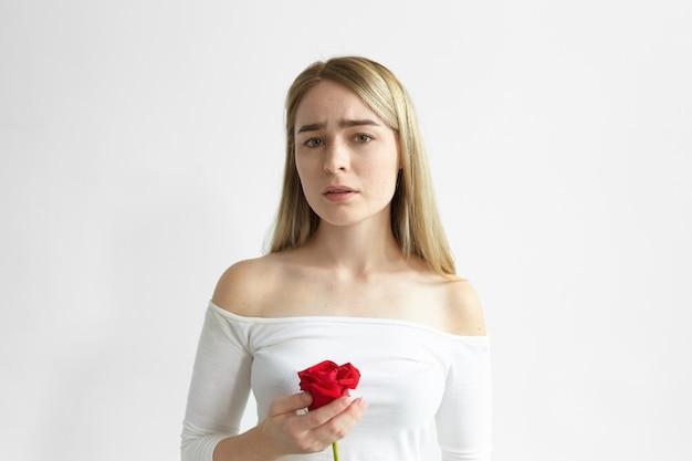 Geïsoleerde foto van aantrekkelijke bezorgde jonge blonde vrouw gekleed in top met open schouders met treurige gezichtsuitdrukking gefrustreerd