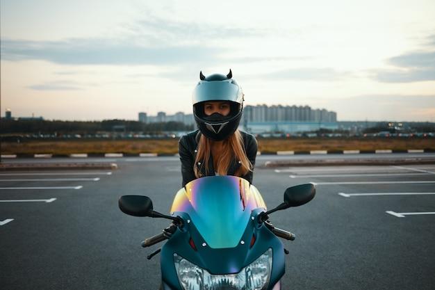 Geïsoleerde foto van blonde vrouwelijke motor racer in speciale beschermingsmiddelen zittend op blauwe motor. extreme, snelheid, adrenaline en moderne actieve levensstijl
