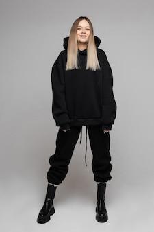 Geïsoleerde foto van een lachende jonge dame poseren in zwarte hoodie met zwarte broek en laarzen op haar. mode concept