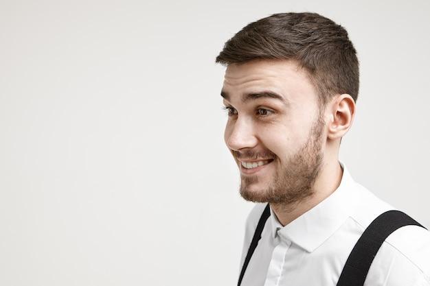 Geïsoleerde foto van emotioneel opgewonden jonge brunette man met stoppels breed glimlachend en wenkbrauwen optrekken, ware verrassing of volledig ongeloof uit, verbluft door positief onverwacht nieuws