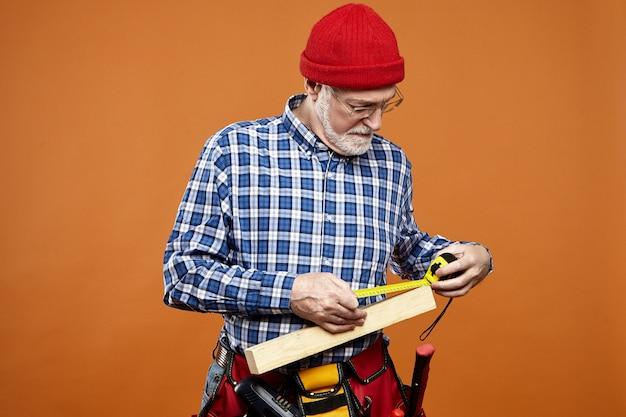 Geïsoleerde foto van ernstige bebaarde senior mannelijke constructeur in bril en hoed met gerichte gezichtsuitdrukking, metingen van houten plank met behulp van meetlint. handmatig werk en arbeid