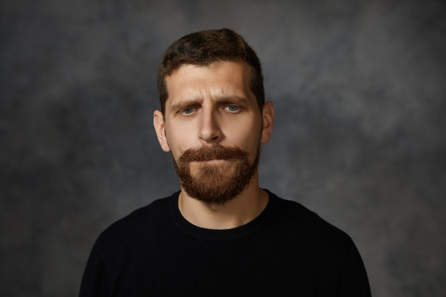 Geïsoleerde foto van knappe gefrustreerde jonge man met dikke baard en snor fronsend, lippen bijtend en neerkijkend met schuldige gezichtsuitdrukking, zich schamen en overstuur voelen of spijt hebben