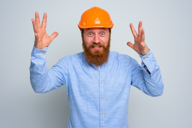 Geïsoleerde gelukkige architect met baard en oranje helm