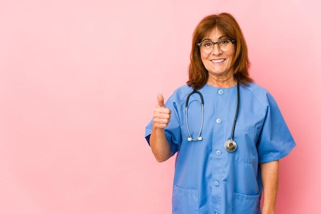 Geïsoleerde glimlachende en duim opheffen van middelbare leeftijd blanke verpleegster