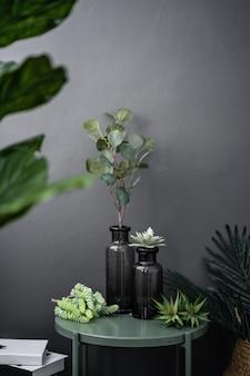 Geïsoleerde gradiënt glazen vaas met kunstplanten op groen metalen bijzettafel in kunstplanten op grijs geschilderde muur