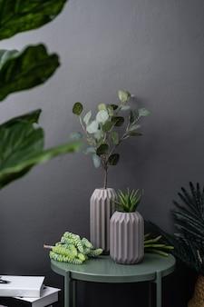 Geïsoleerde grijze keramische vaas met kunstplanten op groen metalen bijzettafeltje in kunstplanten op grijs geschilderde muur