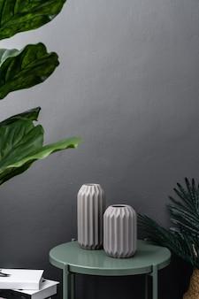 Geïsoleerde grijze keramische vaas op groen metalen bijzettafel op grijs geschilderde muur