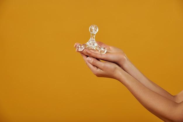 Geïsoleerde handen op de gele achtergrond houden in de palm van je hand een doorzichtige gips stimulator farao