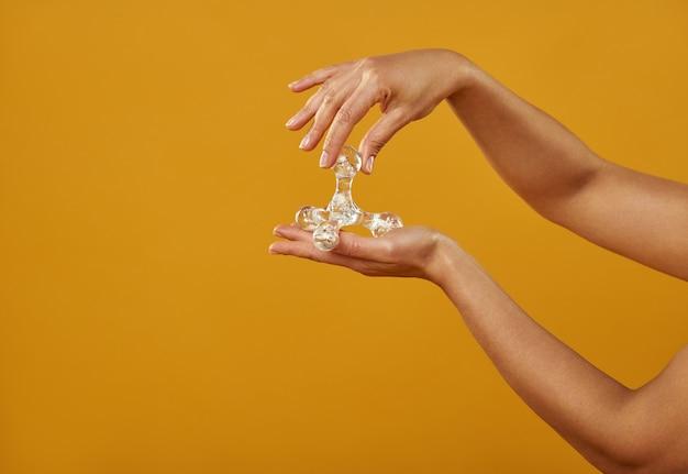 Geïsoleerde handen op een gele achtergrond met een farao massager.