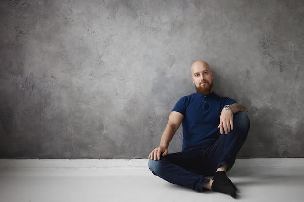 Geïsoleerde indoor shot van aantrekkelijke kale man in stijlvol poloshirt, spijkerbroek en sokken die thuis ontspannen, comfortabel op de vloer zitten met de hand op zijn knie, rust hebben na een dag hard werken op kantoor