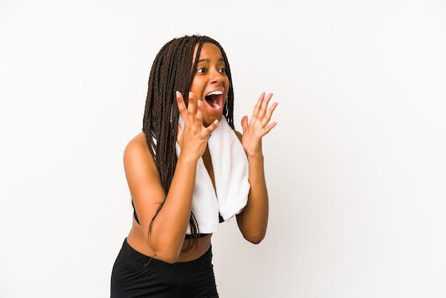 Geïsoleerde jonge afrikaanse amerikaanse sportvrouw schreeuwt luid, houdt ogen open en handen gespannen.