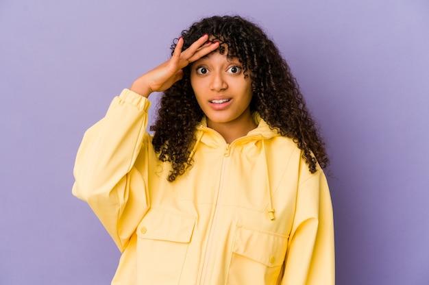 Geïsoleerde jonge afro-amerikaanse afro-vrouw schreeuwt luid, houdt ogen open en handen gespannen.