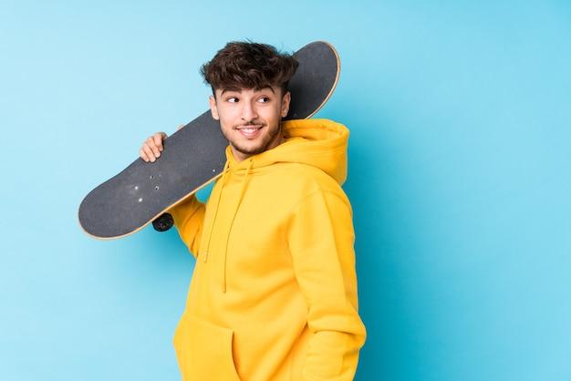 Geïsoleerde jonge arabische skater man kijkt opzij glimlachend, vrolijk en aangenaam.