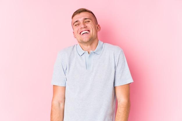 Geïsoleerde jonge blanke man lacht en sluit de ogen, voelt zich ontspannen en gelukkig.