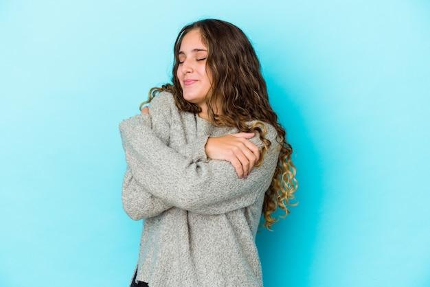 Geïsoleerde jonge blanke vrouw met krullend haar knuffels, zorgeloos en gelukkig lachend.