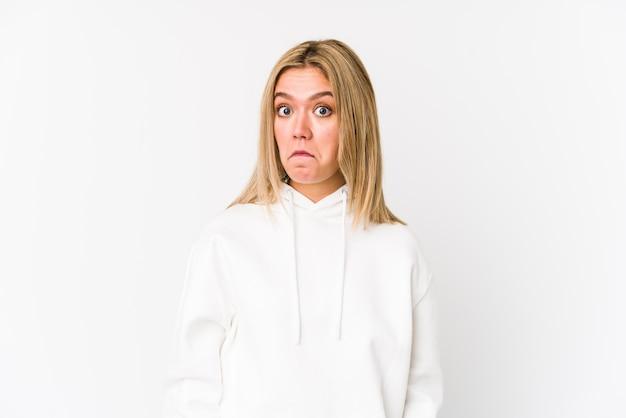 Geïsoleerde jonge blonde blanke vrouw haalt schouders op en opent verwarde ogen.