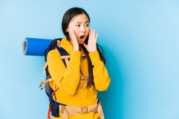 Geïsoleerde jonge chinese backpackervrouw schreeuwt luid, houdt de ogen open en de handen gespannen.