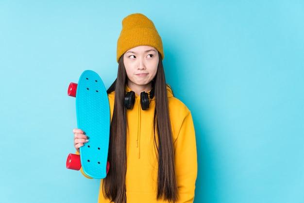 Geïsoleerde jonge chinese schaatsvrouw verward, twijfelachtig en onzeker voelt.