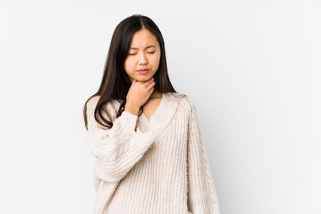 Geïsoleerde jonge chinese vrouw lijdt aan keelpijn als gevolg van een virus of infectie.