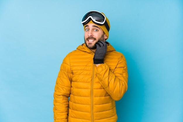 Geïsoleerde jonge skiër blanke man vingernagels bijten, nerveus en erg angstig.