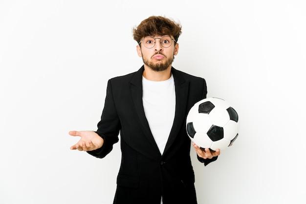 Geïsoleerde jonge voetbalcoach haalt zijn schouders op en opent verwarde ogen