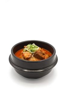 Geïsoleerde kimchi-soep in de zwarte steenkom