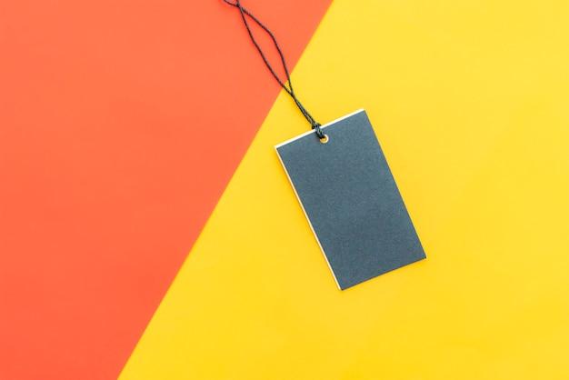 Geïsoleerde kleding prijskaartje met kopie ruimte op rode gele en roze kleur achtergrond.